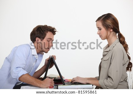 Man helping lady with laptop - stock photo