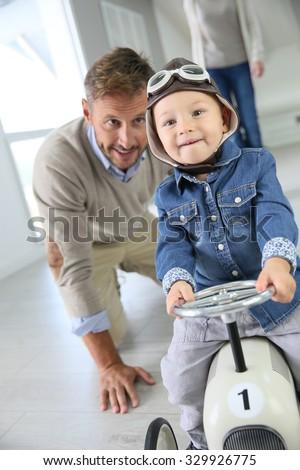 Man helping little boy on a retro toy car - stock photo