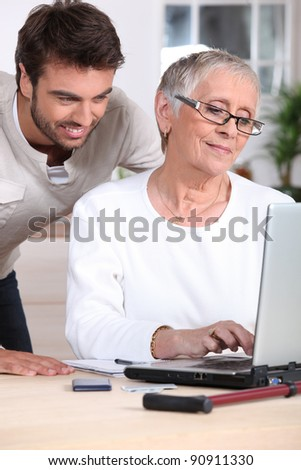 Man helping old lady with computer - stock photo