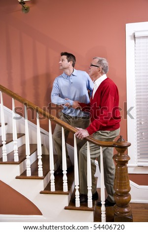Man helping senior father climb staircase at home - stock photo