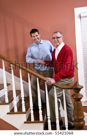 Man helping senior father climb staircase at home - stock photo