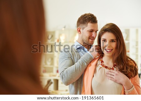 Man helping woman with fitting of a necklace at jeweler store - stock photo