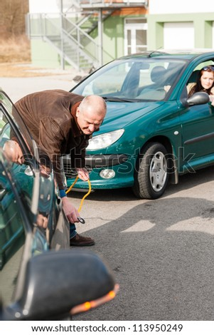 Man helping woman with her broken car problem breakdown cable