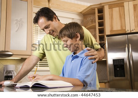 Man helping young boy with homework.  Horizontally framed shot. - stock photo