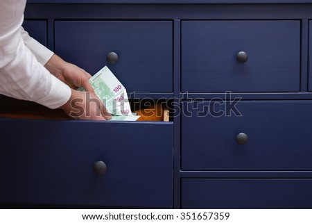 Man hides a salary in euros in a drawer - stock photo