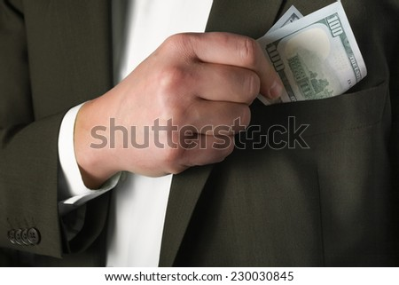 Man hides money in the pocket of green jacket  - stock photo