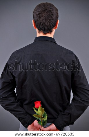 Man hiding a flower behind his back - stock photo