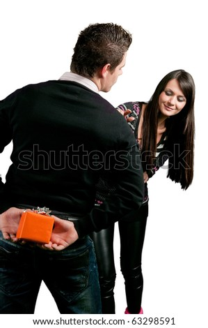 Man hiding a gift for girl behind his back isolated on white
