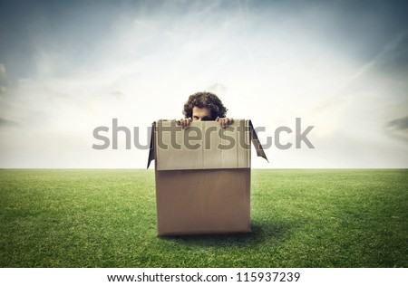 Man hiding behind a box in a large grace field - stock photo
