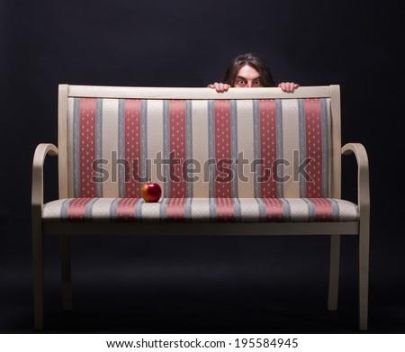 Man hiding behind a retro sofa. - stock photo