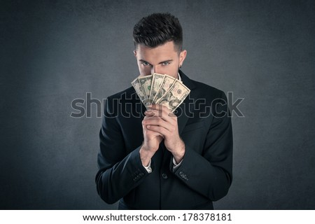 Man hiding behind dollars banknotes with furtive expression against grunge background. - stock photo