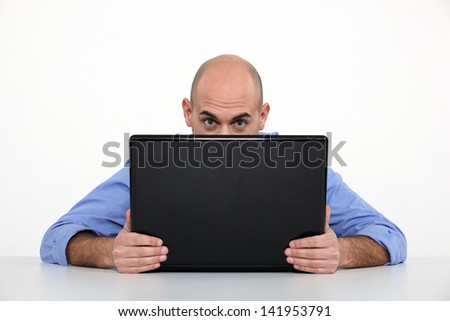 Man hiding behind laptop - stock photo