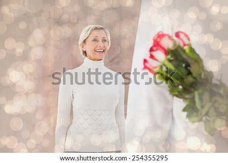 Man hiding bouquet of roses from older woman against light glowing dots design pattern - stock photo