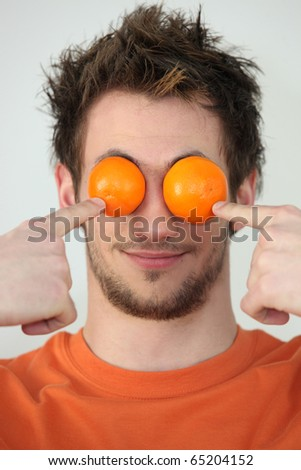 Man hiding his eyes with mandarins - stock photo