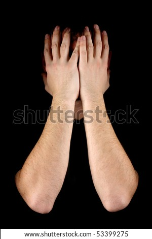 Man hiding his face on black background
