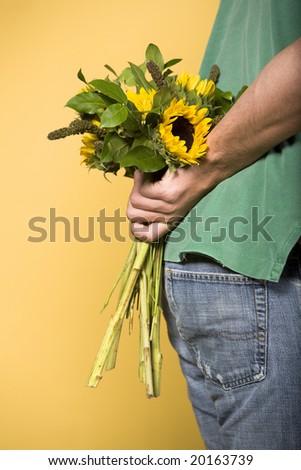 Man hiding sunflowers - stock photo