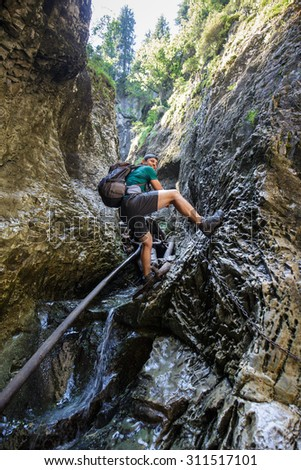 Man hiker climbing on safety chains through a very narrow gorges