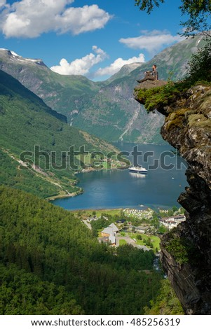 Man hiker enjoying scenic landscapes at a cliff edge, Geirangerfjord