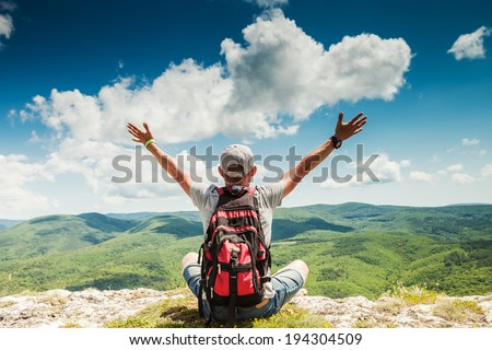 Man hiker greeting rich nature on the top of mountain - stock photo