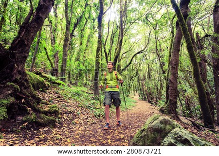 Man hiker hiking in green forest footpath. Young male looking around walking trip or get lost in green beautiful forest, La Gomera, Canary Islands Spain. - stock photo