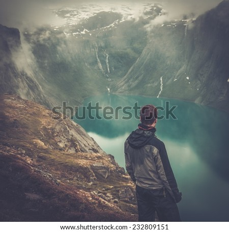 Man hiker in Scandinavian landscape - stock photo