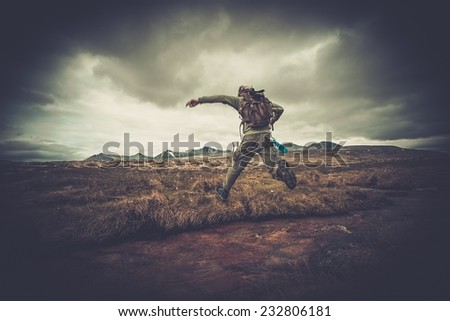 Man hiker jumping across small river