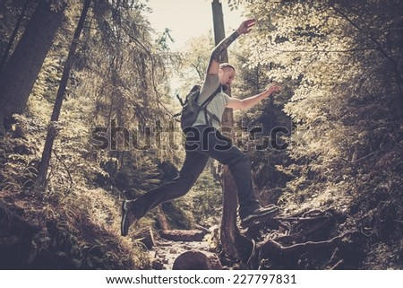 Man hiker jumping across stream in mountain forest - stock photo