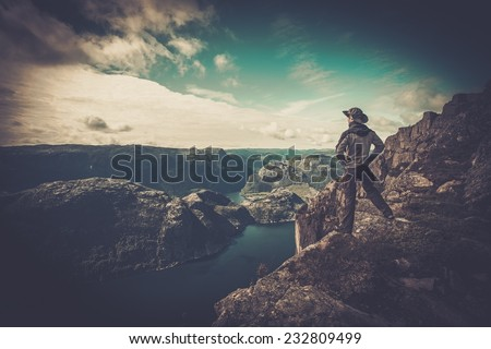 Man hiker looking over fjord panorama - stock photo