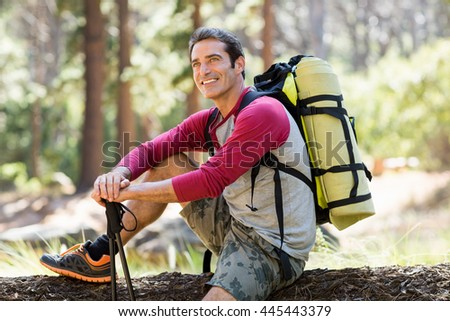 Man hiker smiling and sitting on a tree on the wood