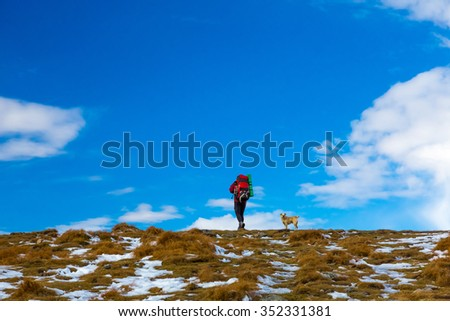 Man Hiker with Backpack and red Jacket walking up with small Dog following him approach to Peak Top with Grass and some snow large copy space filled by blue Sky and Clouds - stock photo