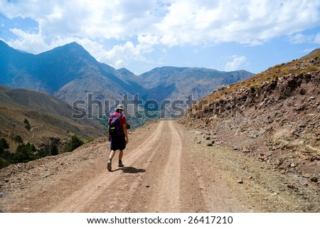 man hiking along track in atlas mountains, morocco - stock photo