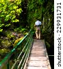 man hiking in bulgarian forest trail just pass small bridge  - stock photo