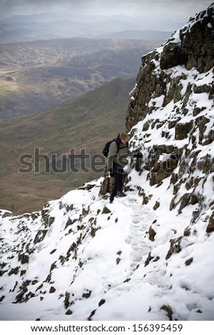 Man hiking in Snowdonia at winter, Crib Goch Mountain. Snowdonia National Park, North Wales, England, United Kingdom, Great Britain, UK, Eng, GB, Europe. - stock photo