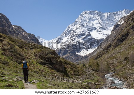Man hiking in the French Alps next to a flowing river with a majestic snow covered peak in the distance - stock photo