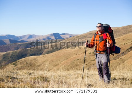 Man hiking in the mountains with a backpack and tent.