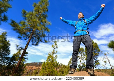 Man hiking reaching summit top cheering celebrating on mountain top with arms up outstretched towards the sky. Happy male hiker. - stock photo