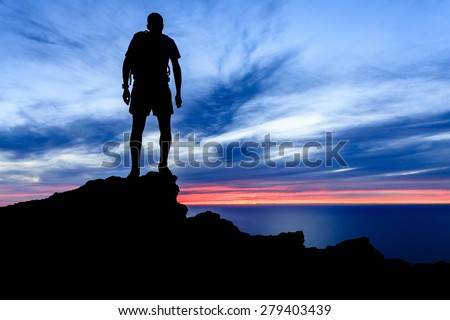 Man hiking silhouette accomplish in mountains, sunset and ocean over beautiful blue sky. Male hiker walking on top of mountain looking at beauty night landscape. - stock photo