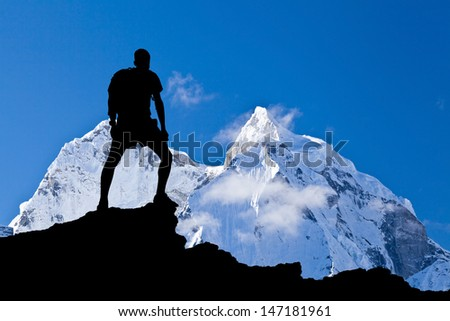 Man hiking silhouette in Himalaya mountains. Male hiker with backpack on top of mountain looking at beautiful night Mount Ama Dablam in Himalayas, Nepal - stock photo