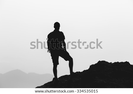 Man hiking silhouette in mountains, inspiration and motivation concept. Hiker with backpack on top of mountain looking at beautiful inspirational landscape. - stock photo