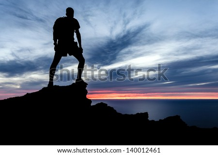Man hiking silhouette in mountains, sunset and ocean. Male hiker with backpack on top of mountain looking at beautiful night landscape. - stock photo