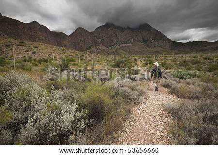 Man hiking through desert towards mountains near storm clouds - stock photo