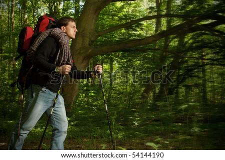 Man hiking through  forested area alone with backpack. Dark edges with motion blur to focus attention on hiker - stock photo