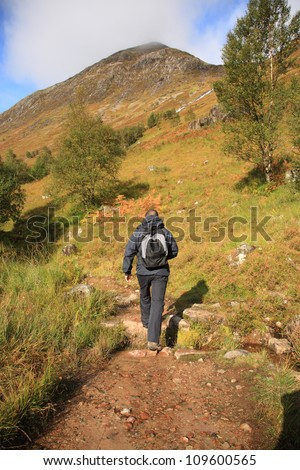 Man hiking through the Scottish hills on a sunny day - stock photo