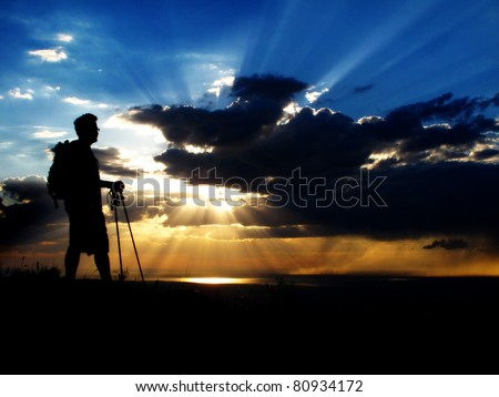 Man hiking up a mountain at sunset or sunrise - stock photo