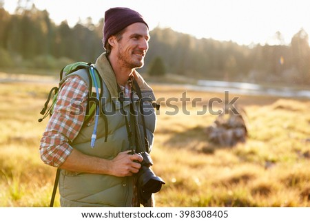 Man Hiking with camera in countryside - stock photo