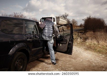 Man hitch-hiking on local European route boarding in car - stock photo