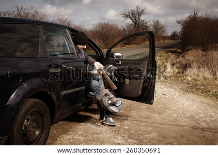 Man hitch-hiking on local European route boarding to car - stock photo