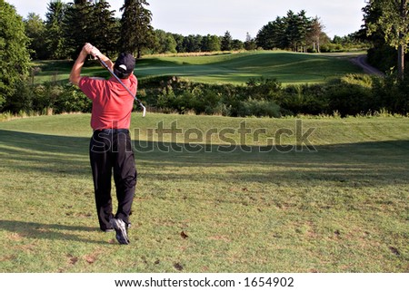 Man hitting a long drive toward the distant green ahead.  Beautiful landscape view of golf course. - stock photo
