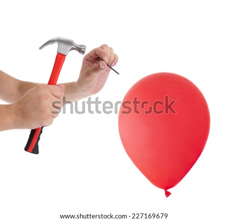 Man hitting a nail into a red balloon on the white background - stock photo