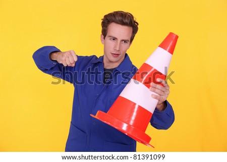 man hitting a traffic cone - stock photo
